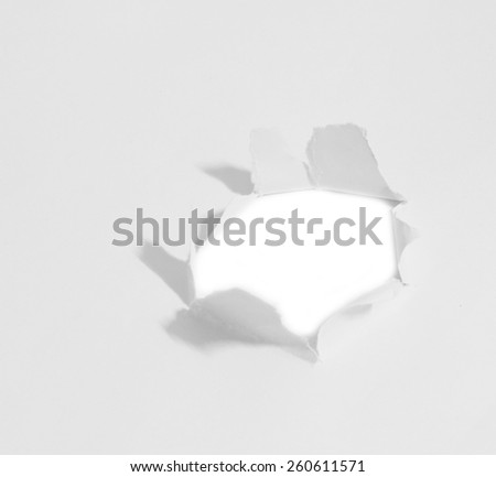 Hole ripped in paper on white - stock photo