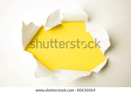 Hole ripped in paper on yellow - stock photo