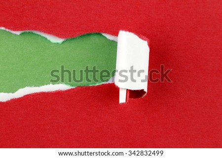 Hole ripped in red paper on green background. Copy space - stock photo