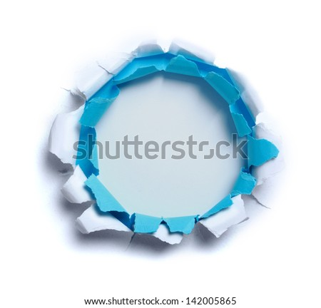 Hole ripped in white and blue paper on light blue background