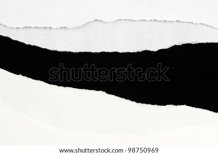 Hole ripped in white paper on black background - stock photo