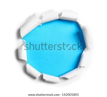 Hole ripped in white paper on blue background
