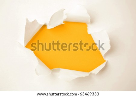 Hole ripped in white paper on orange background. Torn open. Copy space - stock photo