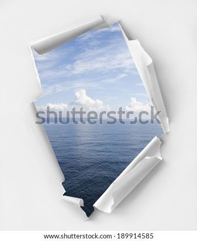 Hole ripped paper with a relaxing seascape view. Clipping path inside - stock photo