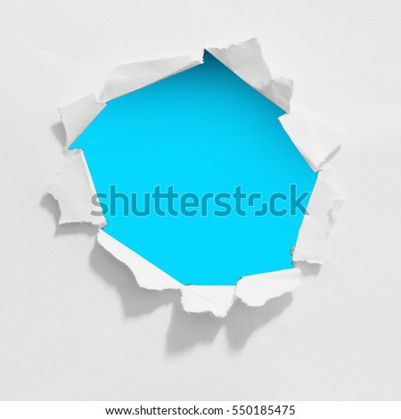 Hole ripped white paper over blue background. copy space for advertising message