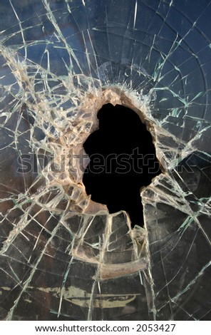 Hole smashed in thick,dirty glass with dark background - stock photo