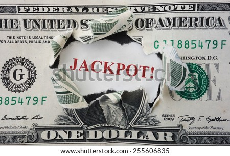 Hole torn in a dollar bill with Jackpot in red                                - stock photo