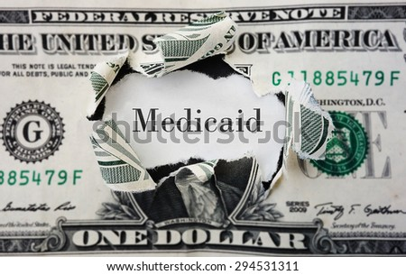 Hole torn in a dollar bill with medicaid text                                - stock photo
