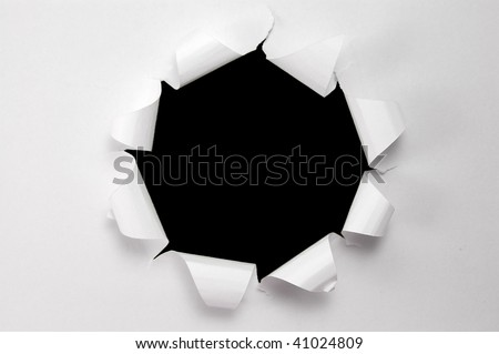 Hole torn in paper on black background - stock photo
