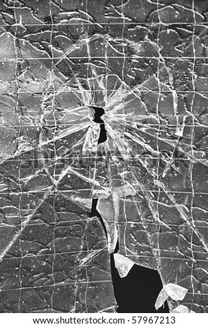 Hole with cracks in the reinforced glass - stock photo