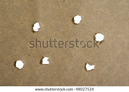 holes from the bullets of paper with hole - stock photo