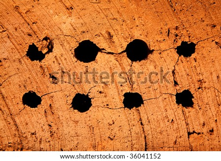 Holes in a solid red brick. - stock photo