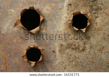 holes with black center in the iron plate - stock photo