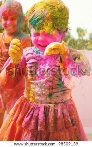 Holi celebrations - Two Indian kids playing Holi in India. - stock photo
