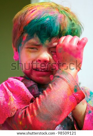 Holi celebrations -Young girl scared of colors on Holi in India. - stock photo