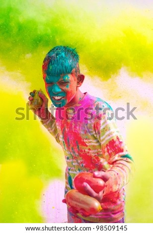 Holi celebrations - Young Indian boy playing with water balloons on Holi festival. - stock photo