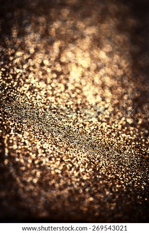 Holiday abstract glitter background with blinking lights and gold defocused texture. Dark Golden  festive bokeh   - stock photo
