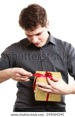 Holiday and special occasion. Young handsome man got golden gift box with red ribbon isolated on white. Guy unwraping present. Surprise. Studio shot. - stock photo