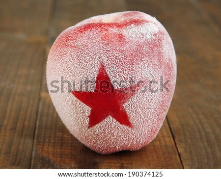 Holiday apple with frosted star on wooden background - stock photo