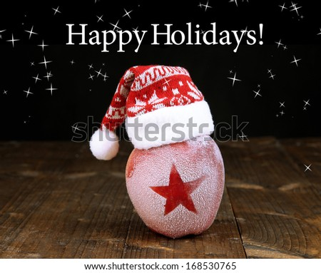 Holiday apple with frosted star on wooden table on black background - stock photo
