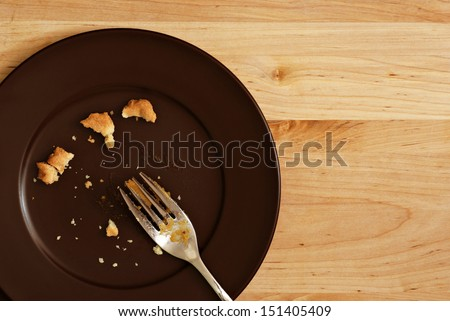 Holiday background image of all that remains of a delicious piece of pumpkin pie.  Plate with crumbs and used fork on wood background with copy space. - stock photo
