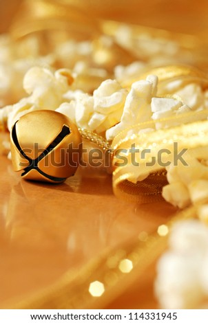 Holiday background image of gold jingle bell with popcorn garland and shiny gold ribbon.  Macro with extremely shallow dof.  Selective focus on bell. - stock photo