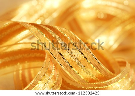 Holiday background image of shiny gold satin ribbon with copy space.  Macro with extremely shallow dof. - stock photo