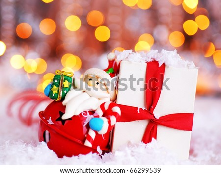 Holiday background with cute Santa Claus Christmas tree decorative ornament & gift box in snow over abstract defocus lights - stock photo