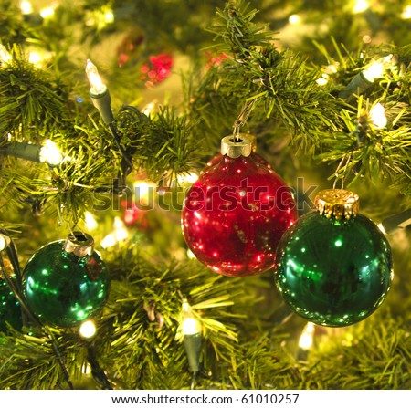 Holiday baubles hanging on Fir tree with sparkling lights - stock photo