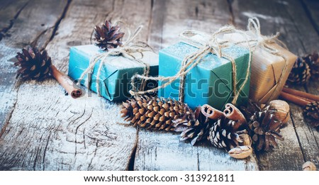 Holiday Blue Boxes with Linen Cord, Cinnamon, Pine cones, Nuts. Natural Gifts on Wooden Background. Toned - stock photo