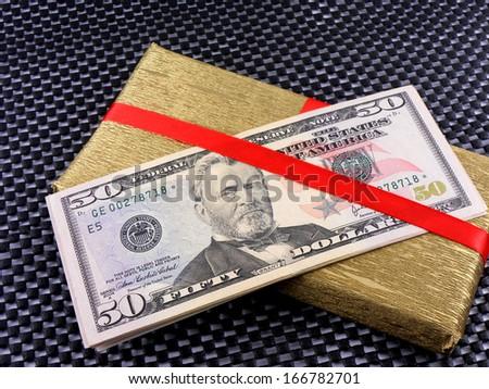 Holiday bonus. Money on red bow decorated gift box - stock photo