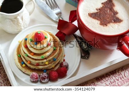 Holiday breakfast / Christmas breakfast with mini pancakes cappuccino tree and syrup on breakfast tray