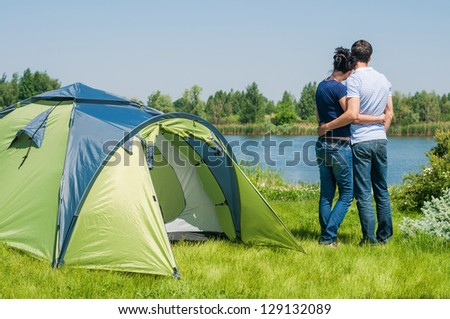 Holiday camping - Man And Woman Couple Camping near A Tent In The Countryside - stock photo