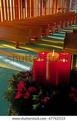 Holiday candles are burning with a wreath in this empty church with sunlight streaming through the stained glass windows.  Vertical photo. - stock photo