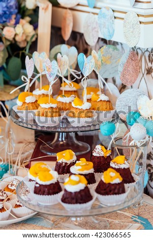 Holiday candy bar. Cupcakes with cream and fruits decorated with paper hearts. - stock photo