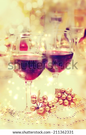 Holiday celebration red wine glasses with festive dinner table setting - stock photo