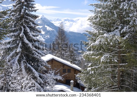 Holiday chalet in winter in the swiss Alps - stock photo