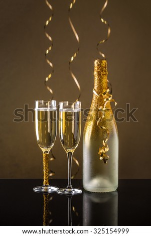 Holiday champagne bottle and two champagne glass