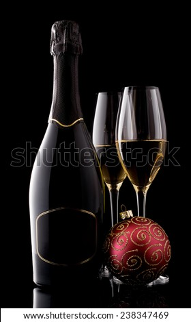 Holiday champagne bottle and two champagne glass on a black with christmas tree decoration - stock photo