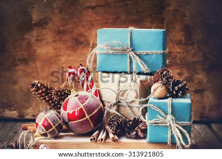Holiday Christmas Composition with Gifts Boxes and Twine, Balls, Pine Cones, Wallnuts, Fir Tree Toys on Wooden Background - stock photo