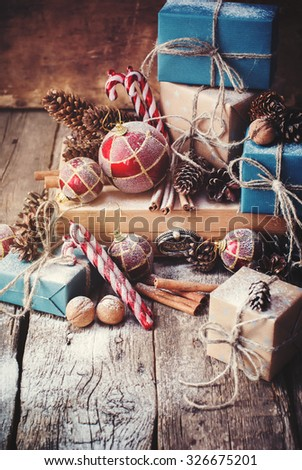 Holiday Christmas Gifts Boxes and Twine, Balls, Pine Cones, Walnuts, Fir Tree Toys on Wooden Background - stock photo