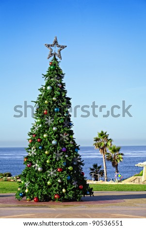 Holiday Christmas Tree Decorating A California Travel And Vacation Location ~ Solana Beach's Fletchers Cove ~ Palm Trees And Walkway Access To The Beach And Ocean Waves - stock photo