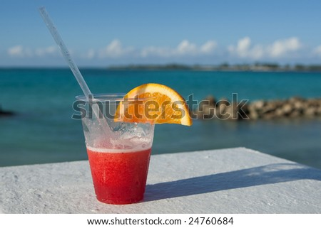 Holiday cocktail resting on balcony overlooking tropical sea