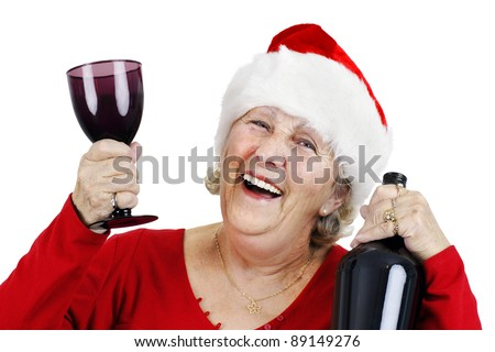 Holiday concept: smiling senior woman or grandmother is wearing Santa Claus's hat and having lots of fun drinking at the Christmas party - stock photo