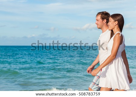 Holiday couple relaxing walking on beach at sunset on honeymoon travel vacation holidays. Young interracial couple in love wearing white dress and shirt, Asian woman and Caucasian man.