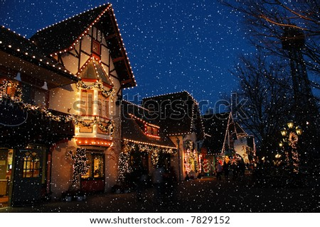 Holiday decorated shopping district in a German village with huge snowflakes falling from a deep blue sky.  Lighted wreaths and strings of christmas lights surround the doorways and windows. - stock photo