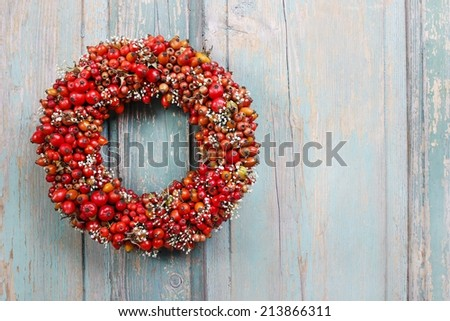 Holiday door wreath with rose hip, hawthorn and rowan berry, copy space - stock photo