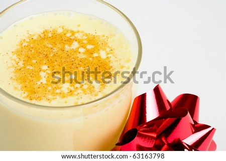 Holiday eggnog with bow against white - stock photo