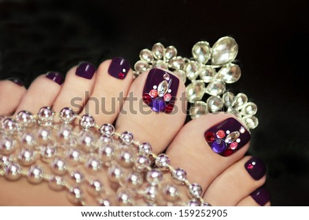 Holiday elegant purple pedicure with rhinestones on a black background with jewelry. - stock photo