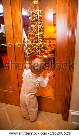 Holiday Excitement as Toddler anticipates opening Christmas Presents under the Christmas Tree.  He has face and hands pressed against the glass for a closer look. - stock photo